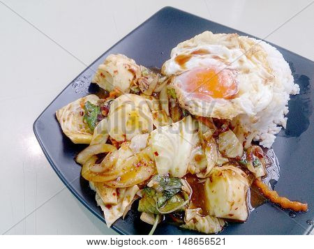 Stir Fried Mixed Vegetables With Roasted Chili Paste , Fried Egg & Thai Jasmine Rice On Black Dish.