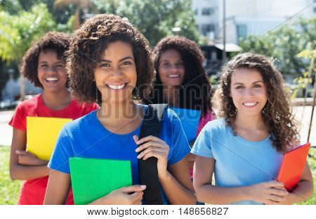 Group of four beautiful brazilian female students outdoor in the city in summer
