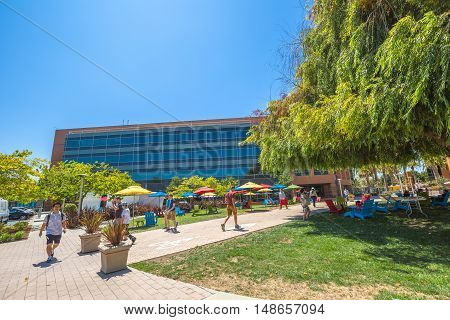 Mountain View, CA, USA - August 15, 2016: Google employees walking in relaxing area at Google's headquarters or Googleplex. Google is a multinational company specializing in Internet-related services.