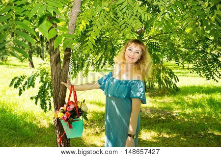 Portrait of the young beautiful smiling woman with hair flowers outdoors