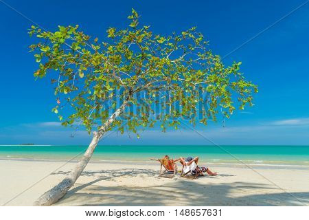 Couple on the beach at tropical resort Travel magazine concept