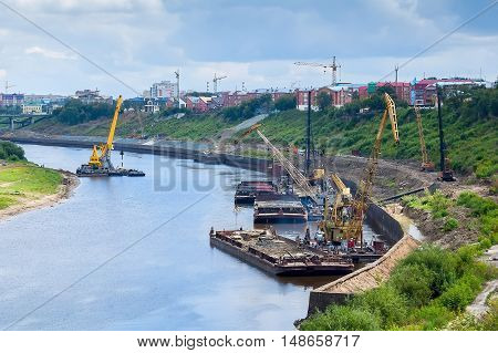 Tyumen, Russia - August 19, 2006: Floating cranes and pile driving machine on barge at construction of pedestrian quay on Tura river