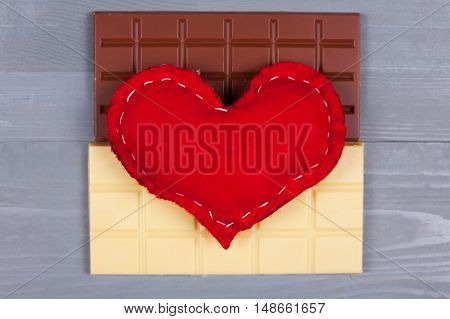 Red homemade heart on top of white and milk chocolate on grey background. Love of sweets and yin and yang concept.