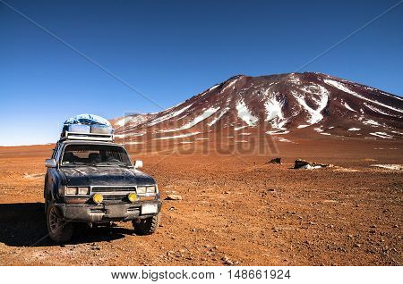 4x4 offroad vehicle in the middle of peruvian highlands with mountain in background