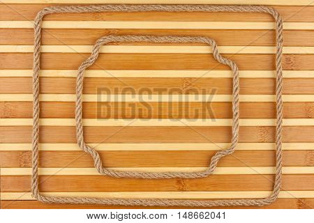 Two frame made of rope lies on a background of a bamboo mat with place for your text