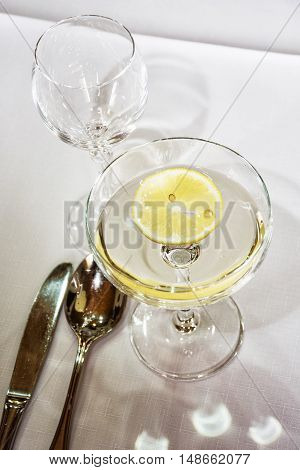 Glasses of vermouth with lemon for birthday party. Refreshments theme. Alcoholic drink. Cutlery.