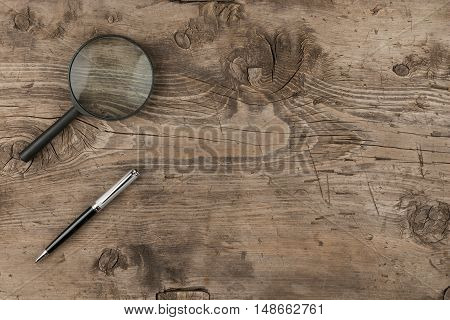 Magnifying glass and a pen lying on old wooden texture top view