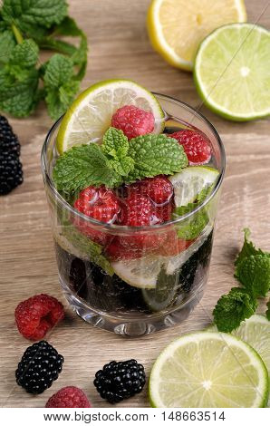 glass of lemonade from the berries of blackberry and raspberry with lime and mint