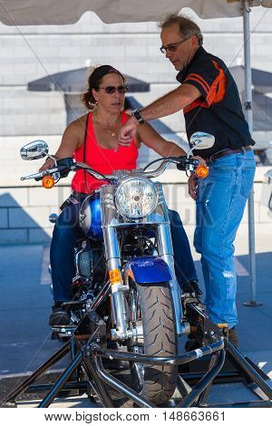 York PA - September 23 2016: A woman attending the Harley-Davidson annual open house receives instruction from factory staff.