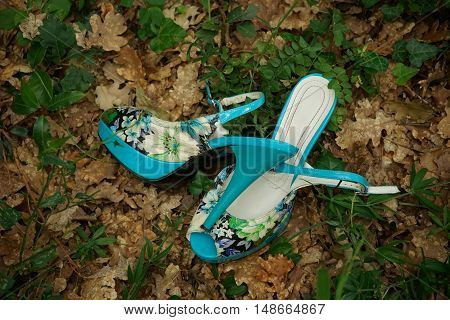 Beautiful summer shoes lie at the ground