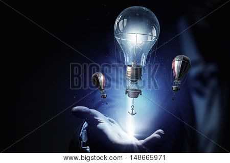 Electric bulb in woman hand . Mixed media