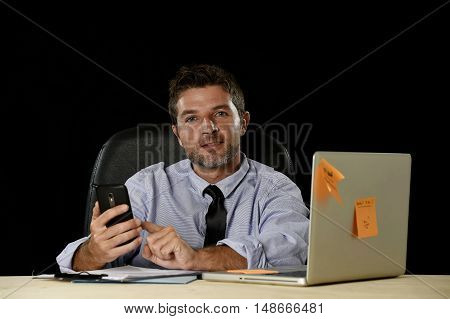 corporate portrait of happy successful businessman in shirt and tie smiling at office computer desk with mobile phone isolated on black background confident and trustful in communication concept