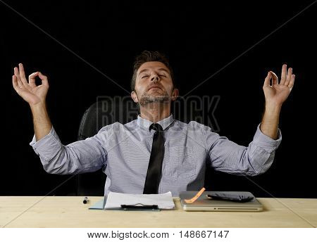 young attractive happy businessman relaxing with hands in yoga position cheerful and friendly wearing shirt and tie isolated in black background sitting at office desk chair in relax at work concept