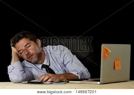 young attractive businessman sleeping wasted and tired at office computer desk in long hours of work late at night and business stress concept isolated in black background