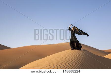 A woman in abaya in sanddunes in Liwa Desert Aby Dhabi UAE