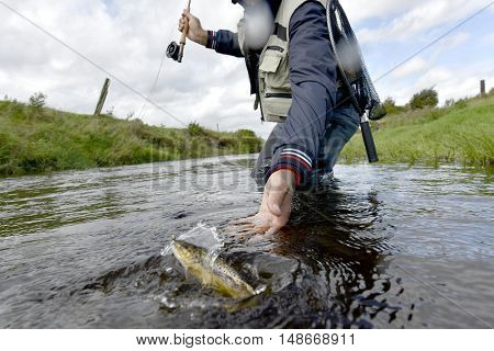 Fly-fisherman catching brown trout in river