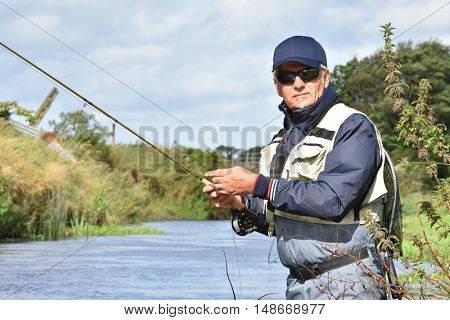 Portrait of fly fisherman in river