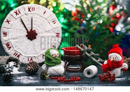 Handmade toy snowman and snowgirl of yarn skeins making beads of red berries over background of knitted clock and shiny Christmas decorations. Color toning