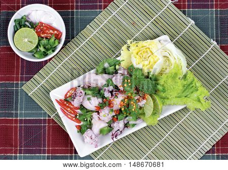 Spicy and sour mixed herb salad with squid wrap minced pork.