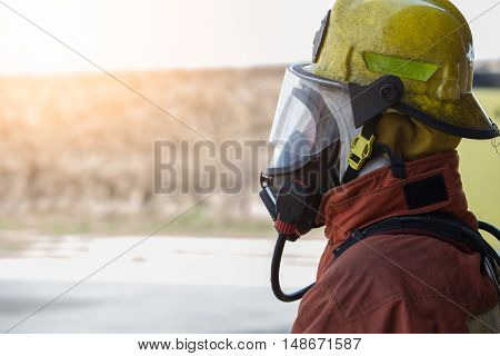 single fireman in fire fighting protection suit with flare