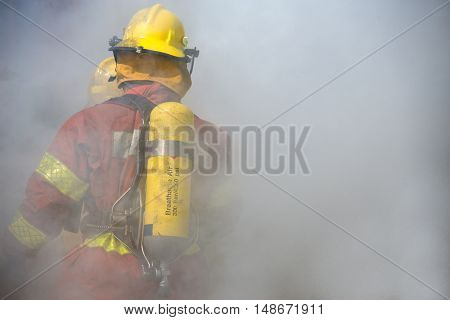 fireman in fire fighting suit working surround with smoke