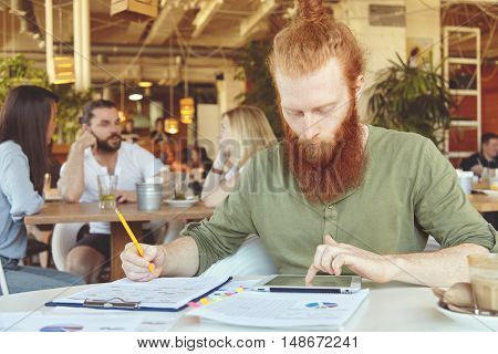 Bearded Student Working On Course Paper, Making Research, Analyzing Statistics On Tablet, Writing Do