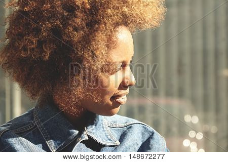Beautiful African Lady With Afro Hairstyle And Nose-ring, Standing Outdoors Against Gray Wall With C