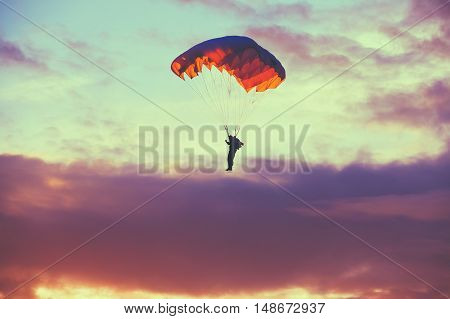 Skydiver On Colorful Parachute In Sunny Clear Sky. Active Hobbies. Purple Colors Sunset Or Sunrise Sky.