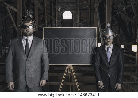 Two vintage businessman with an empty blackboard indoor