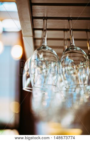 Glasses hanging over bar rack. Glasses for wine above a bar rack
