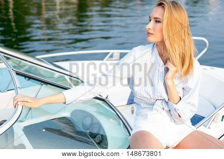 model tests of fashion blond girl in shirt posing in the dock on the boat by the sea