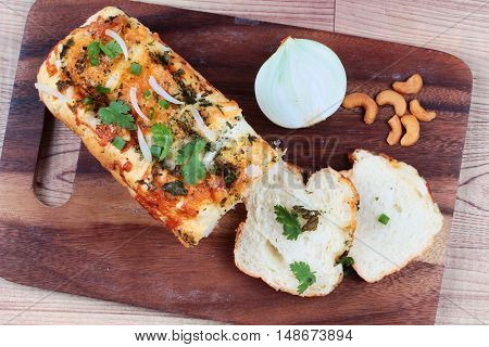 Homemade spinach bread with halves onion and cashew nuts on butcher served.