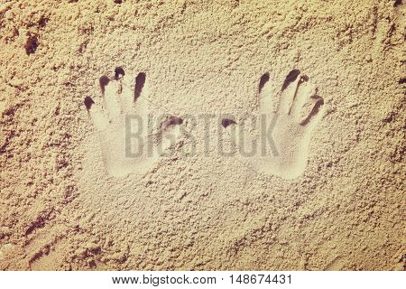 Top view of sandy beach with hand shapes, handprint