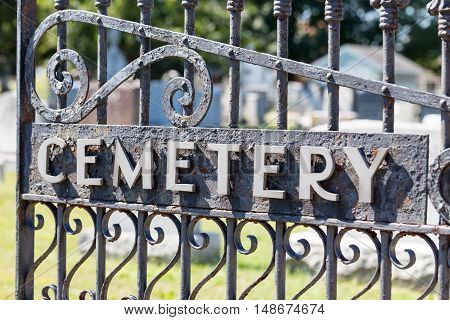 Close Up of Black wrought iron cemetery gate.