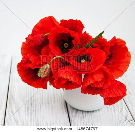 Red poppies in a vase on a wooden table