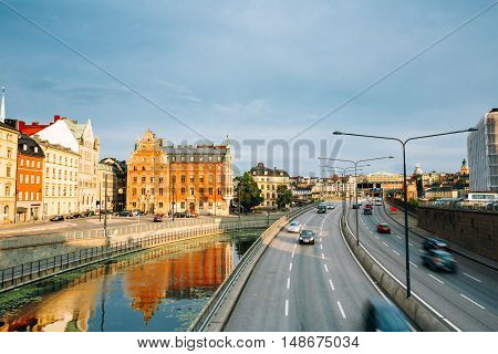 Stockholm, Sweden. The View Of Embankment And Centralbron Highway With Moving Cars In Gamla Stan In Summer Sunny Evening Day.