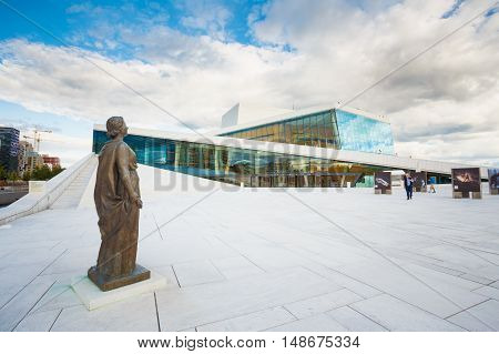 Oslo, Norway - July 31, 2014: Side View Of Glass Facade Of Oslo Opera And Ballet House. The Bronze Statue On White Marble Granite Floor Surface Under Cloudy Summer Sky.