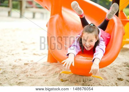 Cute happy girl is playing on playground outdoor