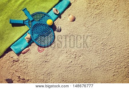 Top view of sandy beach with summer accessories and tennis rocket