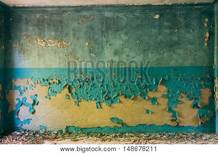 Wall With Cracked And Peeling Surface Of Blue And Brown Or Yellow Paint.