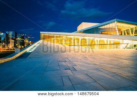 Oslo, Norway - July 31, 2014: The Side View Of Brightly Illuminated Glass Facade Of Norwegian National Opera And Ballet House In Summer Evening, Blue Sky Background.