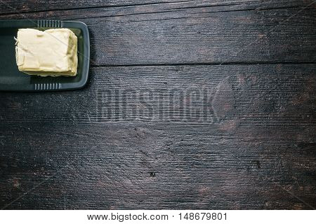 Block of fresh milk butter on the plate. Flat lay