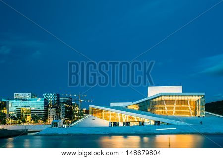 Oslo, Norway - July 31, 2014: The Scenic Night Evening View Of Illuminated Norwegian National Opera And Ballet House Among Contemporary High-Rise Buildings. Blue Sky Background, Copyspace.