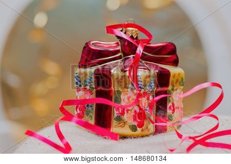 Close up of decorative Christmas decoration at a gift box with red ribbons on a gold blurred background. Selective focus on the box