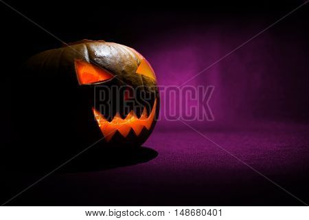 The Carved Face Of Pumpkin Glowing On Halloween On Purple Background
