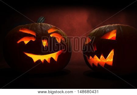 Two Carved Faces Of Pumpkins Glowing On Halloween On Red Background