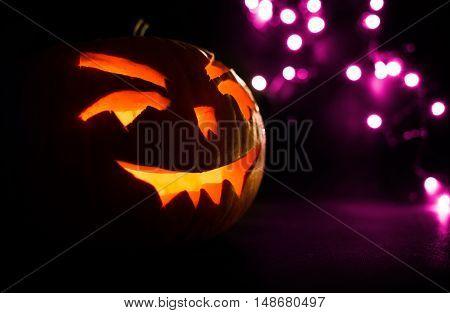 Carved Face Of Pumpkin Glowing On Halloween On Purple Bokeh Light Background
