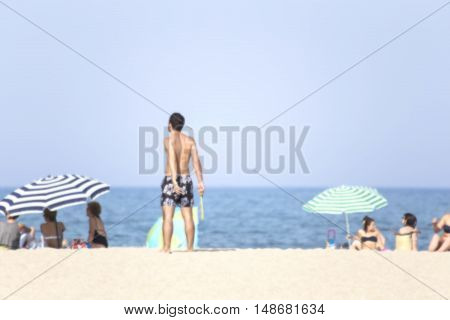 Blurred image of the Mediterranean beach with swimmers