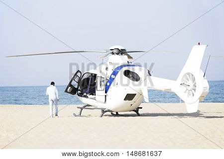 The white ambulance helicopter on a sand beach