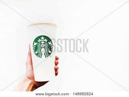 Imatra, Finland September 9: Person holding Starbucks coffee to go recycling paper cup for hot beverages with company logo in hand isolated on white background with copy space.